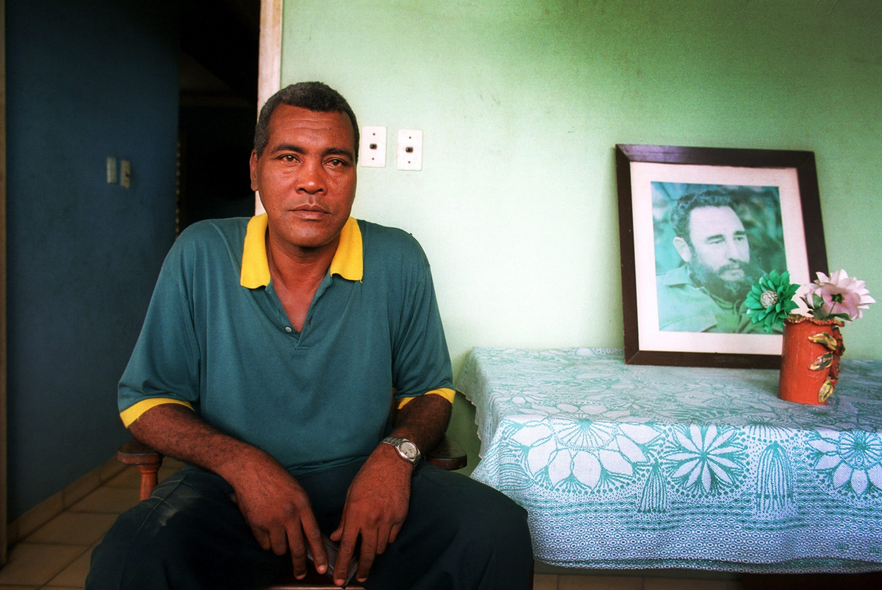 DELICIAS, CUBA - JULY 30: Cuba's boxing legend Teofilo Stevenson sits next to a photo of Cuba's Revolution leader Fidel Castro in his home in Delicias on July 30, 2000, in the eastern province Las Tunas, Cuba. Stevenson, who won 3 Olympic Gold medals and was 3 times World Champion, died of heart attack at the age of 60 on June 11, 2012, in Havana, Cuba. (Photo by Sven Creutzmann/Mambo photo/Getty Images)